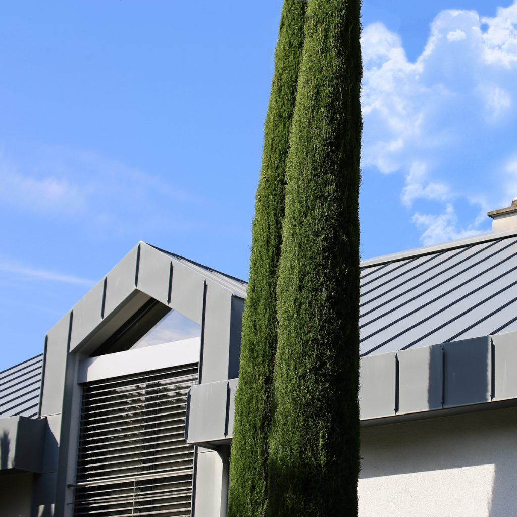 grey metal roofing on a grey building with a tree