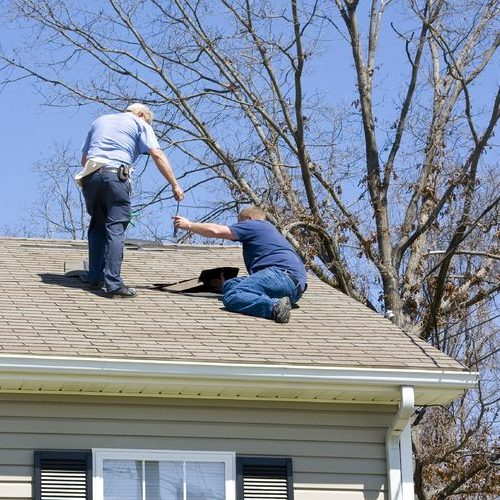 A Picture of Two Men Looking at a Roof.